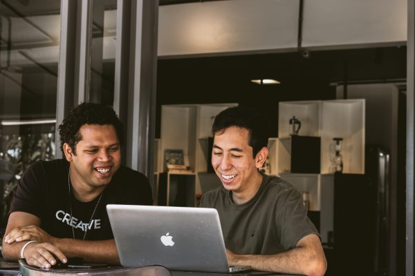 Two men working on a Mac laptop and smiling at the screen
