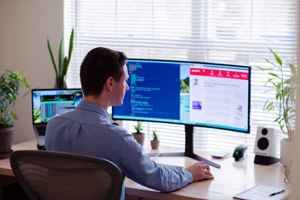 Man in a blue collared shirt sitting at a desk with plants with three computer monitors and evaluating lease accounting software platforms.