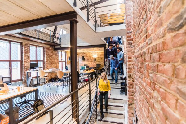 Group of coworkers walking down an open set of metal stairs in a modern office
